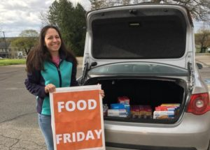 """Community member Christy Fieldsa displays a sign during a recent """"Food Friday"""" at The Factory Ministries. (Photo provided by The Factory Ministries)"""