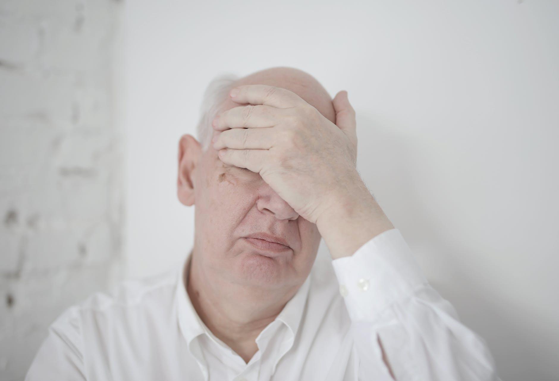 senior hand on face
