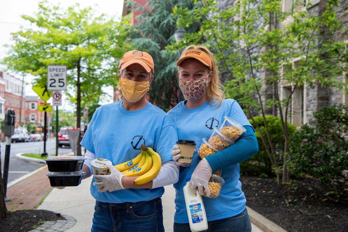 Anchorage Breakfast Program volunteers Jolyn Gibbel, left, and Estie Valle show off some of the items distributed in Anchorage's daily grab-and-go breakfasts outside the First United Methodist Church, Anchorage's home base. (Photo: Fosterjfoster Productions)
