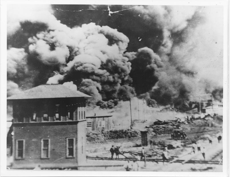 "In this archive photo from 1921, smoke rises in Tulsa, Oklahoma, where a white mob destroyed the city's ""Black Wall Street"" business district. (Source: McFarlin Library, University of Tulsa)"