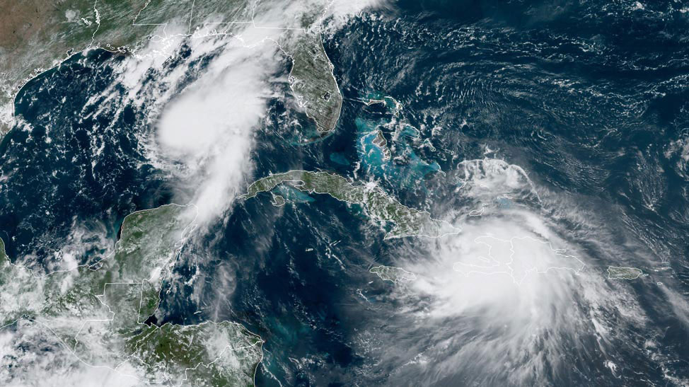 Tropical storms Marco, left, and Laura, lower right, make their way through the Caribbean in this satellite image. (Source: NOAA)