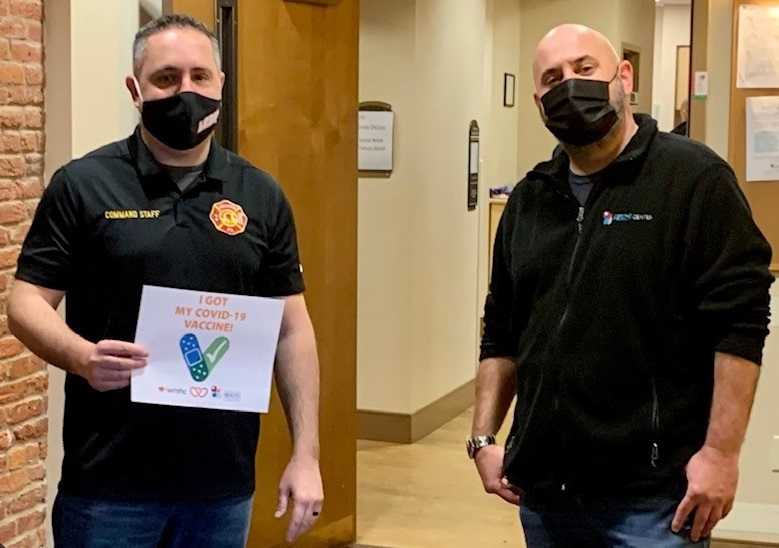 "Lancaster city Fire Chief Scott Little, left, displays his ""I Got My Covid-19 Vaccine"" sign after his vaccination at the Lancaster Health Center on Saturday, Jan. 2, 2020. He is accompanied by James Reichenbach, the center's chief mission advancement and community programs officer. (Photo: Provided)"