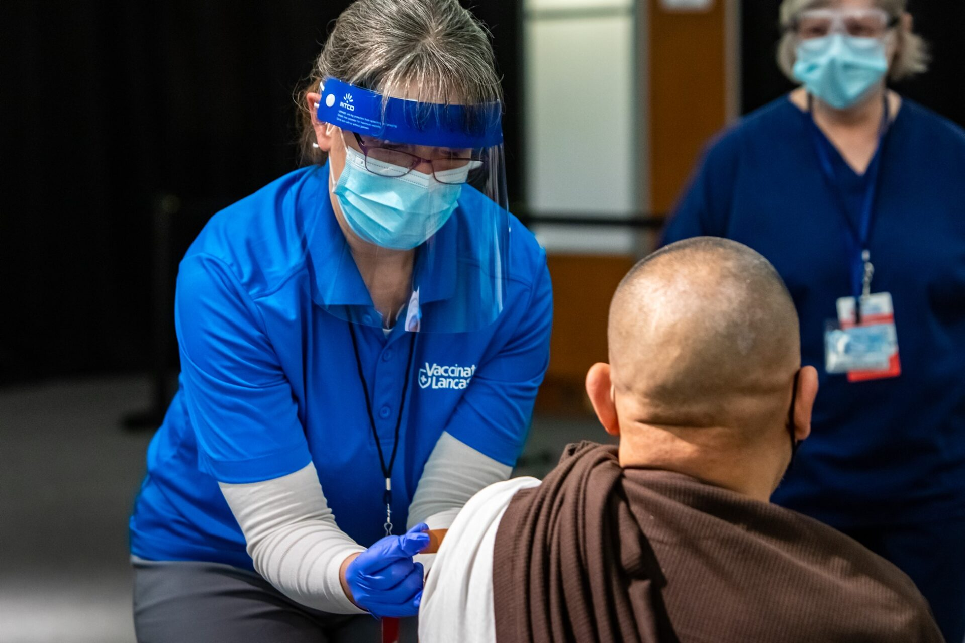 A staff member inoculates a patient with a Covid-19 vaccine at the Vaccinate Lancaster community vaccination center on its opening day, Wednesday, March 10, 2021. (Source: Provided)