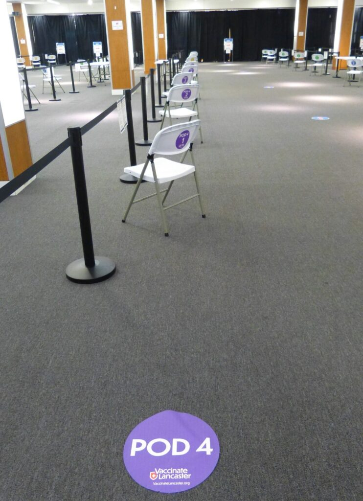 A decal on the floor marks where patients wait before entering a vaccination pod at the Vaccinate Lancaster Community Vaccination Center on Tuesday, March 9, 2021. (Photo: Tim Stuhldreher)