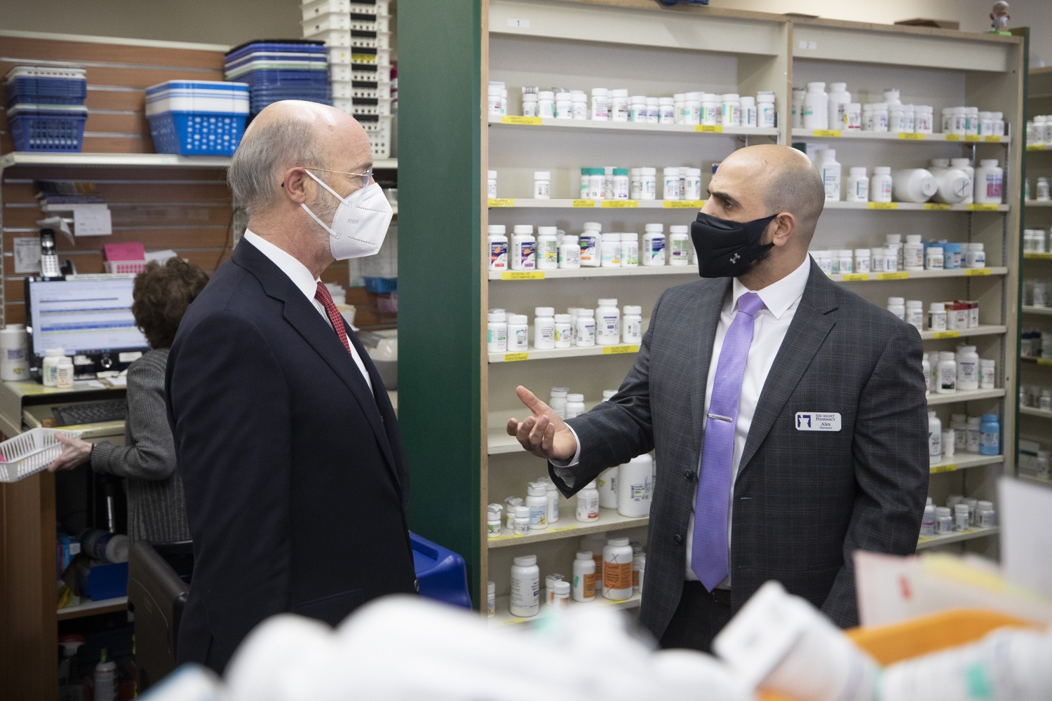 Gov. Tom Wolf, left, talks with pharmacist Alex Quaddoumi of See-Rite Pharmacy in Harrisburg before a press briefing outside the pharmacy on Thursday, April 22, 2021. (Source: Pa.gov.)