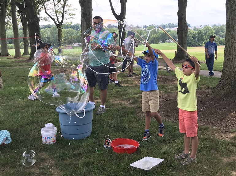 Children make giant soap bubbles at a SAAL picnic. (Source: Provided)