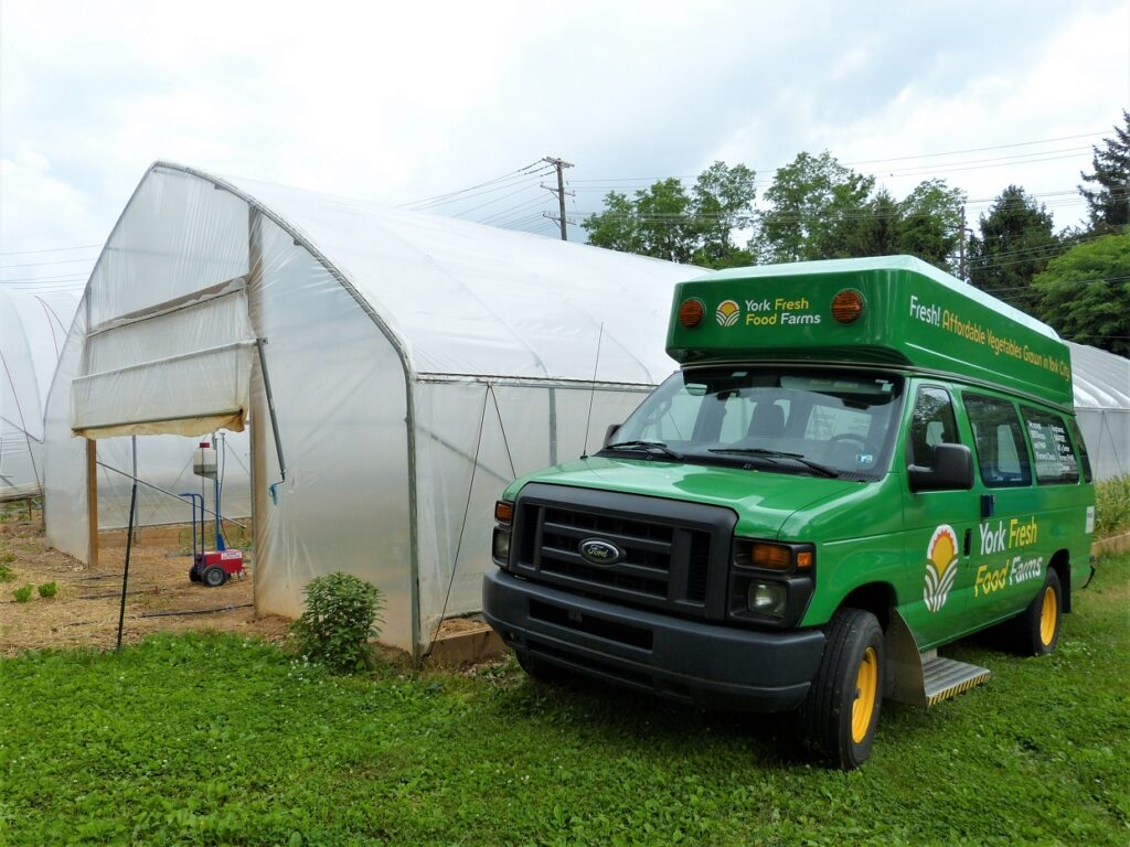 The newer of York Fresh Food Farms' two Mobile Produce Market vehicles sits next to a high tunnel on at the farm;s Willis Road headquarters. (Photo: Tim Stuhldreher)
