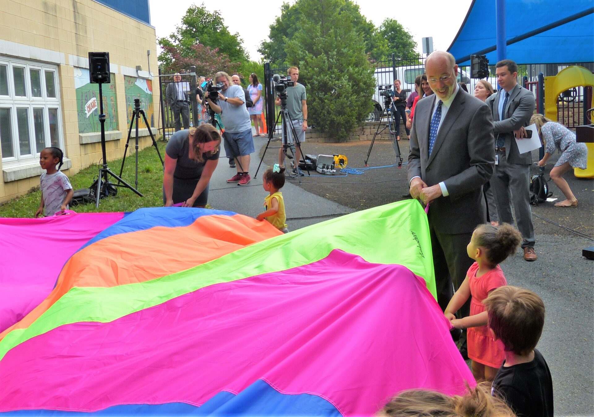 Gov. Tom Wolf takes part in a game with a parachute in the playground at Community Action Partnership of Lancaster County on Thursday, July 8, 2021. Acting Health Secretary Meg Snead is second from left. (Photo: Tim Stuhldreher)