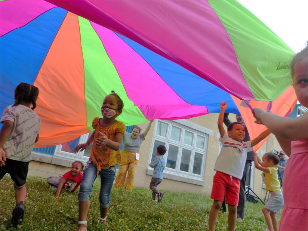 Children run under a parachute during a game at Community Action Partnership of Lancaster County on Thursday, July 8, 2021. (Photo: Tim Stuhldreher)