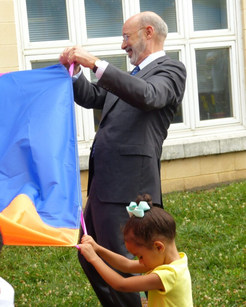 Gov. Tom Wolf takes part in a game with a parachute in the playground at Community Action Partnership of Lancaster County on Thursday, July 8, 2021. (Photo: Tim Stuhldreher)