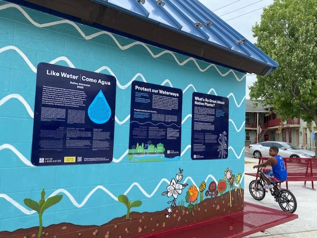 Signs on the pavilion wall explain the importance of waterway and native plant conservation in both English and Spanish. (Photo: Olivia Smucker)