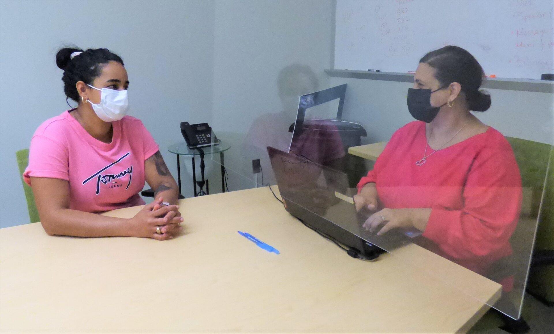 Client Luz Medina, left, talks with career navigator Marisol Sanchez at Tec Centro in Lancaster on Thursday, July 8, 2021. The plexiglass partition between them is a Covid-19 precaution. (Photo: Tim Stuhldreher)