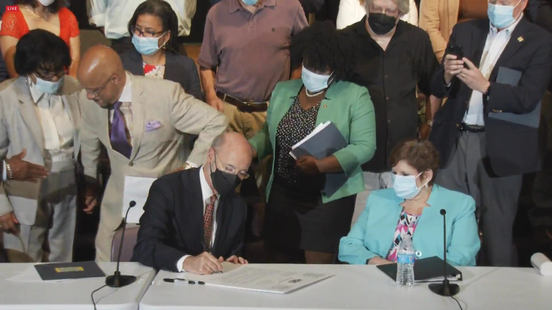 Gov. Tom Wolf signs a letter calling on state Republicans to advance a $15 minimum wage bill such as the one sponsored by state Sen. Christine Tartaglione, D-Philadelphia, who is looking on at right. (Source: Pa.gov)