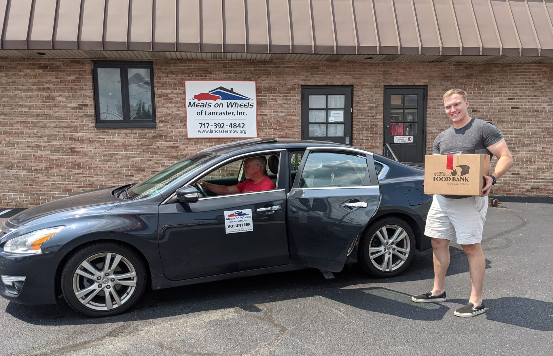 Intern Noah Jordan loads a Senior Food Box into a car driven by Doug Hopwood, Meals on Wheels of Lancaster's director of program and volunteer development, outside the nonprofit's headquarters on Manheim Pike on Thursday, July 22, 2021. (Source: Meals on Wheels of Lancaster)