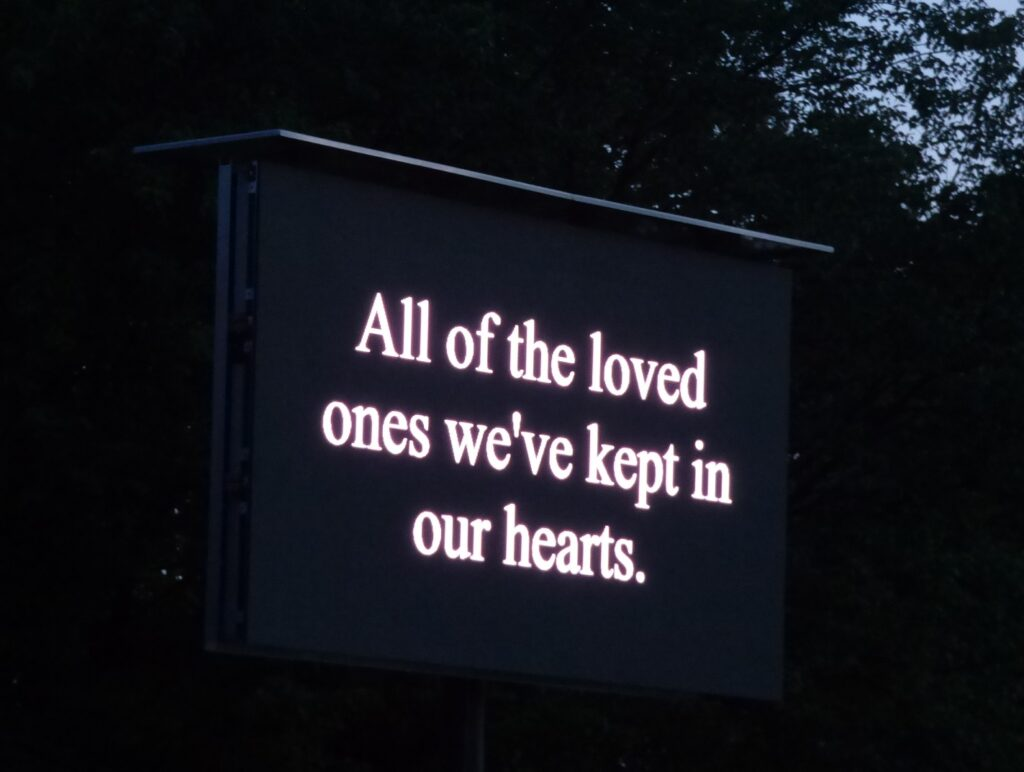 """Messages are displayed on a billboard during a candlelight ceremony concluding """"A Day of Healing"""" at Longs Park on Thursday, Aug. 12, 2021. (Photo: Tim Stuhldreher)"""