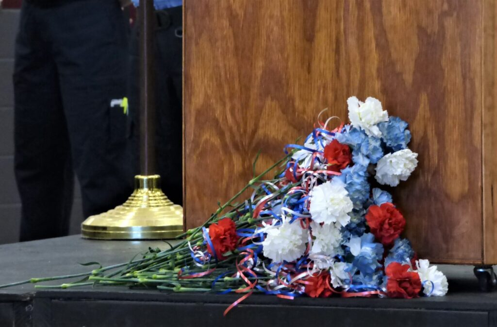 A flower was laid before the podium for each of the 52 Lancaster County first responders who died in the line of duty. (Photo: Tim Stuhldreher)