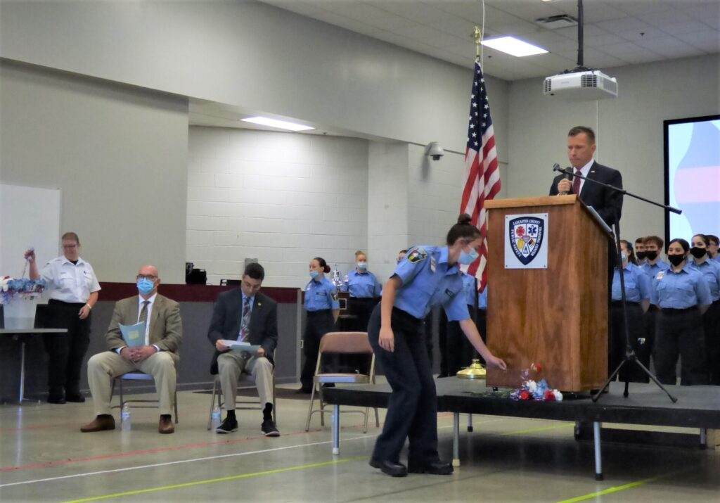 A cadet lays a flower before the podium in honor of a fallen Lancaster County first responder as County Commissioner Josh Parsons reads the first of three section of names. (Photo: Tim Stuhldreher)